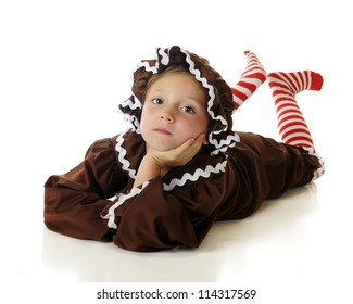 "An attractive elementary ""gingerbread girl"" laying on her belly, clicking her candy-striped heals together.  On a white background."