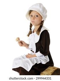 An attractive elementary Pilgrim girl sitting on a log with a mouth full of roast chicken.  On a white background.
