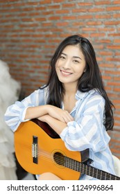 Attractive emotional smiling Asian Thai woman singing and playing acoustic guitar. Beautiful woman singer playing musical instrument indoors. People, music, joy and fun , she looks at camera