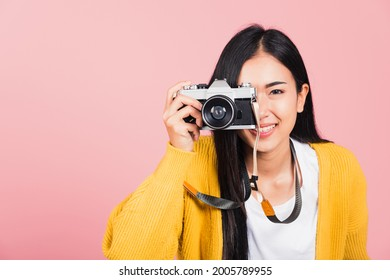 Attractive energetic happy Asian portrait beautiful young woman smiling photographer taking a picture and looking viewfinder on retro vintage photo camera ready to shoot isolated on pink background