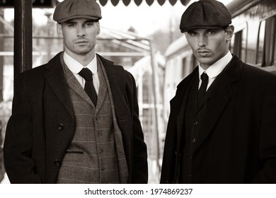 Attractive English gangsters smoking at railway station with train in the background