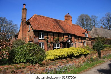 Attractive English medieval brick and timber cottage with garden wall and shrubs