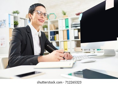Attractive entrepreneur with stylish haircut sitting at desk and writing down creative ideas in notepad, interior of spacious office on background