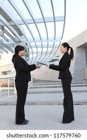 An attractive ethnic business women team at office building with report