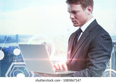 Attractive european businessman using laptop on abstract city background with business interface. Double exposure