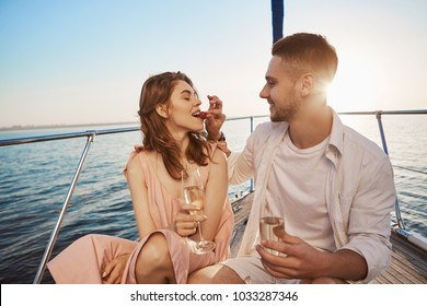 Attractive european couple on a summer vacation, enjoying sailing on board of yacht, drinking champagne. Boyfriend promised her to spend holidays together so he bought boat tour.