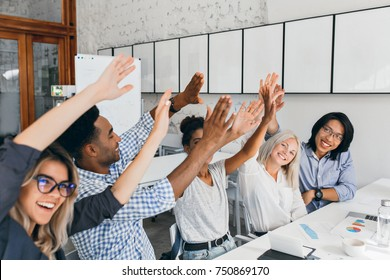Attractive european girl waving hands with friends, happy for successful meeting. African and asian office workers having fun during conference and laughing.