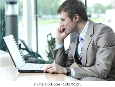 Attractive european guy talking on phone while using laptop.