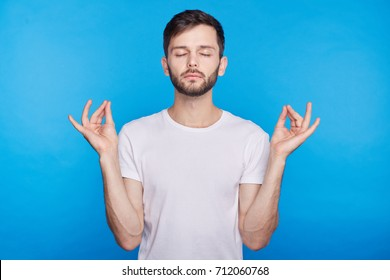 Attractive European hipster with peaceful expression meditating, holding his hands in mudra gesture, keeping his eyes closed while practicing yoga in office, trying to calm down and relax on break.