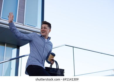 Attractive European male college student wearing shirt standing outside university building, turning back and waving hand, saying goodbye to his groupmates, carrying leather bag and coffee-to-go