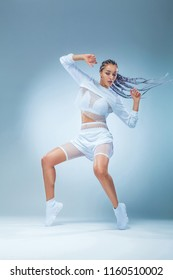 Attractive excited fitness girl dancer in sportwear dance isolated over blue background. Fashion and livestyle concept.