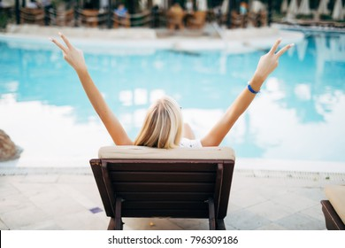 Attractive excited young woman with raised hands enjoying summer vacation near pool.
