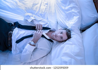 Attractive exhausted businessman lying on bed looking up at camera as he unfastens his tie