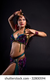 Attractive and exotic bellydancer in a purple costume and with brass zills