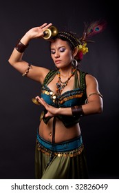 Attractive and exotic bellydancer in tribal costume with zills on her fingers