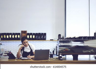 Attractive experienced barista working in cafeteria with modern design loft interior making accounting documentation in online database. Female coffee shop cashier standing against copy space wall