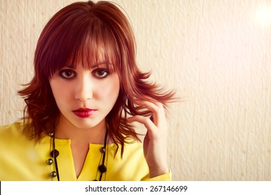 Attractive face of young girl in yellow blouse with chic hairstyle.
