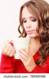 Attractive fall girl long hair red autumnal sweater holding white mug with coffee warm beverage. Woman warming herself
