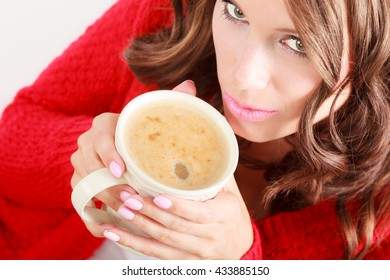 Attractive fall girl red autumnal sweater holding white mug with coffee warm beverage.Woman warming herself relaxing top view close up