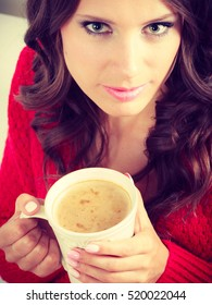 Attractive fall girl red autumnal sweater holding white mug with coffee warm beverage, sitting on sofa at home. Woman warming herself relaxing top view