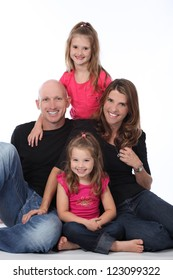 Attractive family of four, with mother, father and two daughters, wearing pink and black in studio on white isolated background