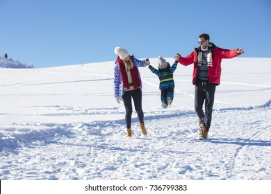 Attractive family having fun in a winter park on mountain