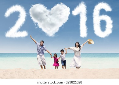 Attractive family running together on the beach while celebrating new year with cloud shaped numbers 2016