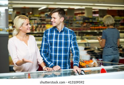 Attractive family standing near display with frozen food in supermarket