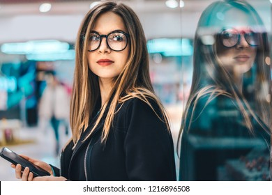 Attractive fashion blogger standing near show-window in a mall with mobile phone in hands and writing a rewiew about the shop she visited. Shopping, black friday sale, blogging, freelancing concept