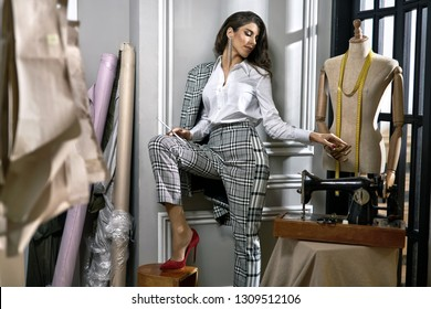 Attractive fashion designer holds a pencil and a hand of a mannequin in the workshop with sewing machine and cloth rolls. She wears a gray checkered suit with white shirt and red shoes. Horizontal.