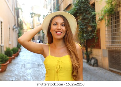 Attractive fashion girl in Trastevere, Rome. Beautiful smiling woman with yellow dress and hat walks through the streets of Rome, Italy.