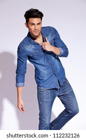 attractive fashion man posing and looking at the camera on gray background