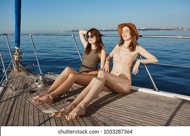 Attractive fashionable model in bikinis getting tan on boat with closed eyes and pleased smile while sailing in sea. Friends decided to hide from freezing winter and travel to tropic islands.