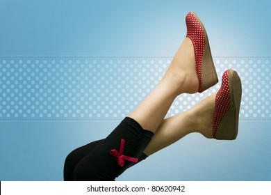 Attractive feet high up, showing red polka dotted shoes, against a vignette blue background with polka dots.