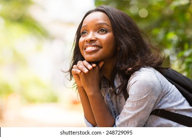 attractive female african college student daydreaming
