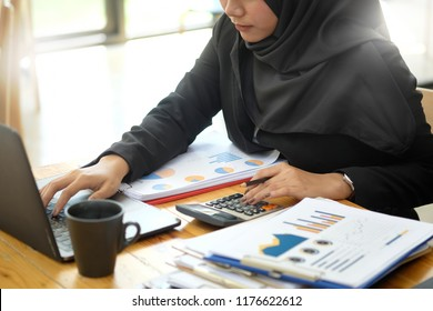 Attractive female Arabic corporate worker working on laptop computer on desk