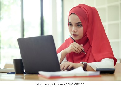Attractive female Arabic working on laptop computer and paperworks on desk