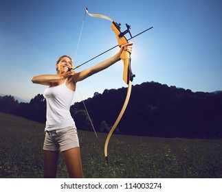 Attractive female archer bending a bow and aiming in the sky