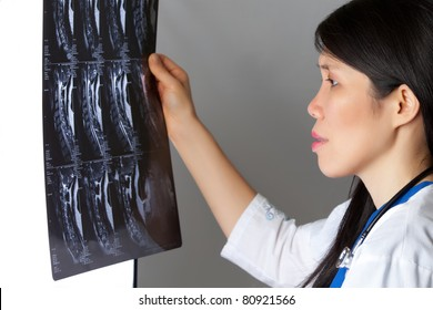 Attractive female Asian Doctor looking at MRI white lab jacket and stethoscope