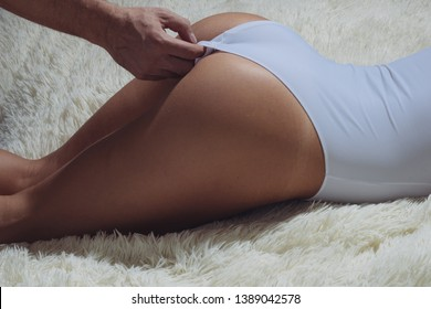 Attractive female ass. Erotic massage. Sensual touch. Sexual stimulation. Perfect buttocks. Male hands undressing sexy woman. Female buttocks stripped by male hand. Sexy buttocks white lingerie.