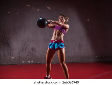 Attractive female athlete performing a kettle-bell swing.
