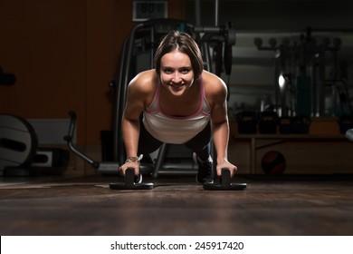 Attractive Female Athlete Performing Push-Ups On Floor