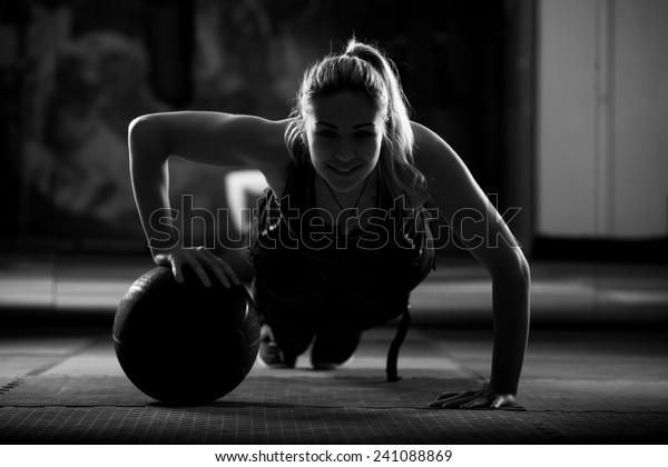 Attractive female athlete performing push-ups on medicine ball.Medicine ball push up.Low key