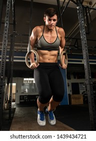 An attractive female athlete with strong abs is doing ring dips at the barbell rack. Fitness sports in a gym. The athletic and short-haired woman is strained during the workout.
