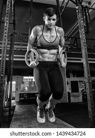 An attractive female athlete with strong abs is doing ring dips at the barbell rack. Fitness sports in a gym. The athletic and short-haired woman is strained during the workout. Black and white.