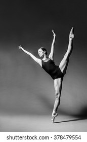 Attractive female ballet dancer in black custome and ballet shoes dancing in studio. Grayscale image.