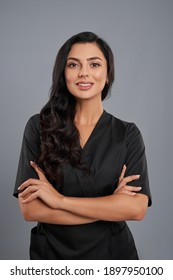 Attractive female beautician in black uniform standing with crossed arms over grey background. Positive cosmetologist with long dark hair smiling and looking at camera.