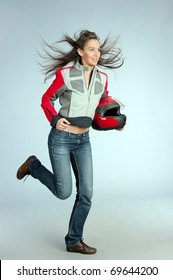 Attractive female biker with fly-away hair, dressed in jacket and holding red motorbike helmet.