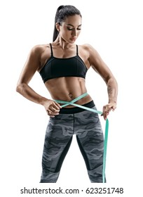 Attractive female bodybuilder measuring her waist with measurement tape. Photo of young woman in sportswear on white background. Strength and motivation