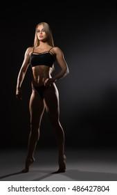 Attractive female bodybuilder posing at camera